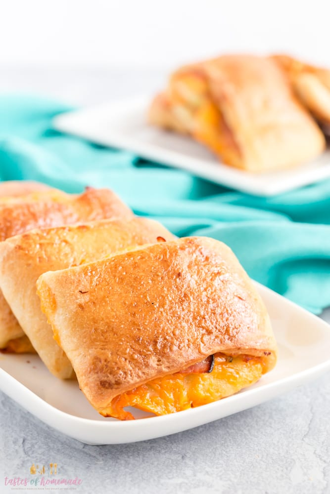 Ham and cheese roll on a plate with cheese oozing out of roll