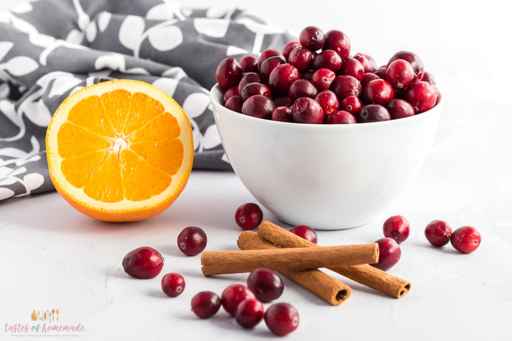Cranberries, fresh oranges, and cinnamon sticks on a table.