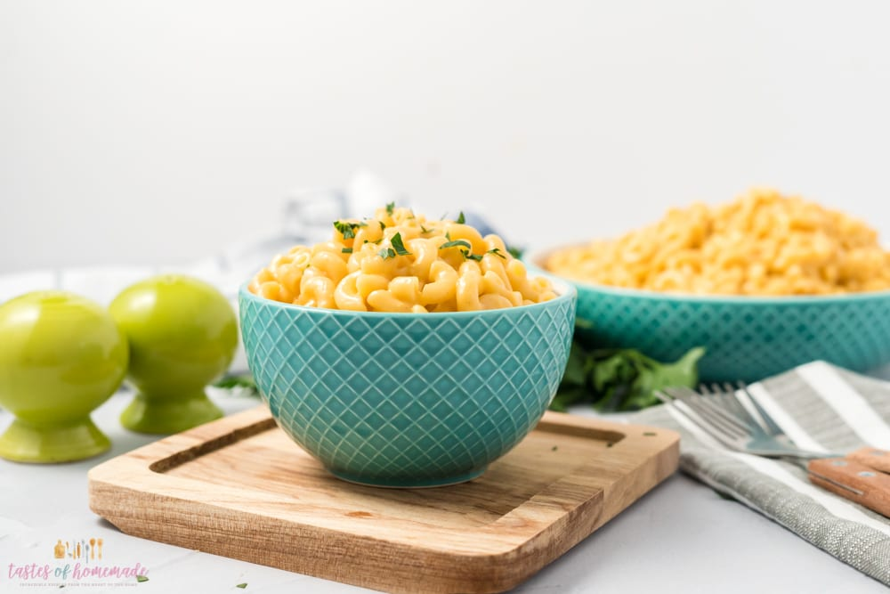 Macaroni and cheese in a blue bowl with salt and pepper shakers beside it.