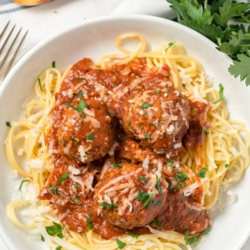 A pile of spaghetti in a bowl with 3 meatballs and tomato sauce