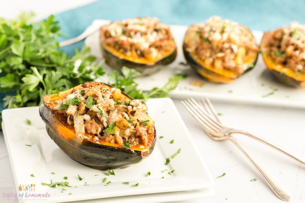 Acorn squash, stuffed with sausage and mushrooms on a square plate