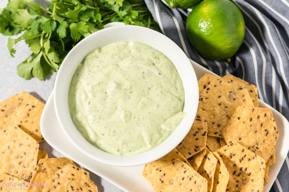 A bowl of cilantro lime yogurt dressing in a white bowl surrounded by tortilla chips.