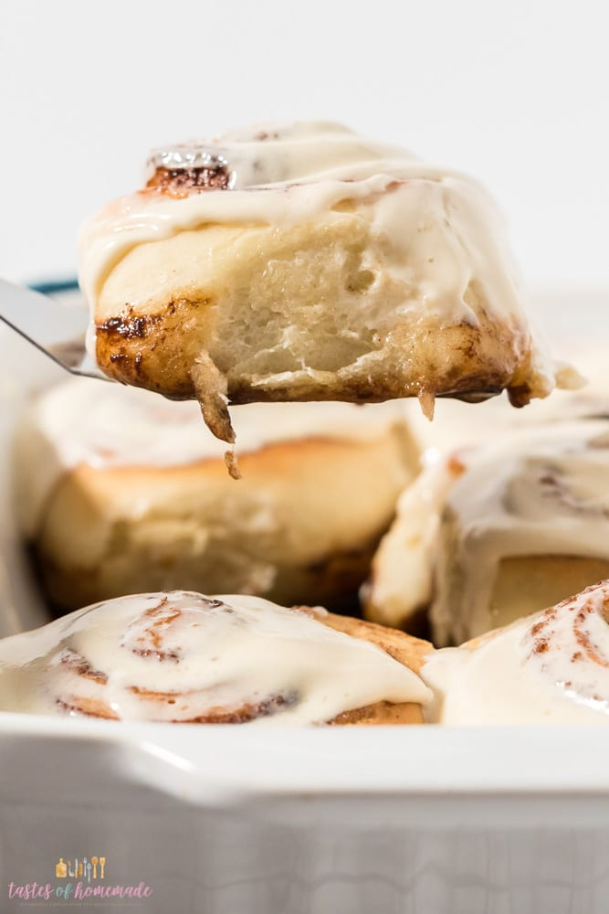 Cinnamon roll being lifted from a pan