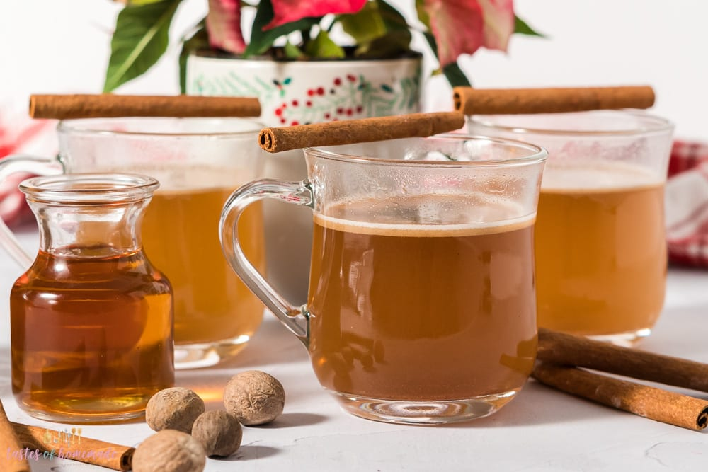 Hot buttered rum in mugs with cinnamon sticks