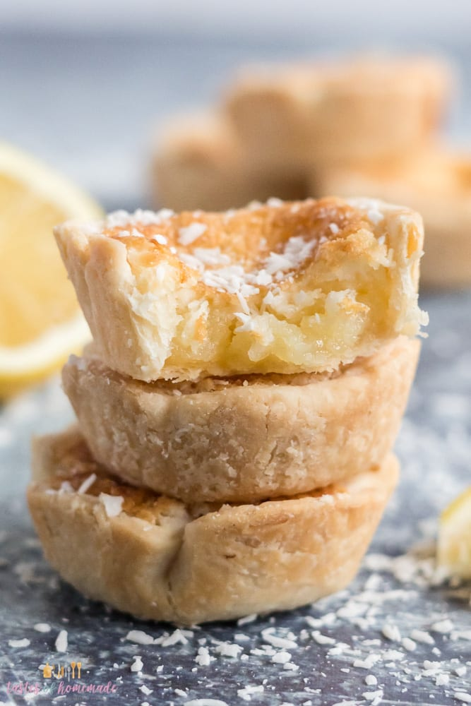 Lemon tarts in a stack with a bite taken out of the top one.