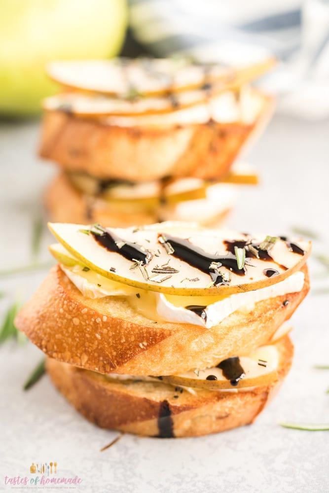 Pear and brie crostini with balsamic vinegar on a table