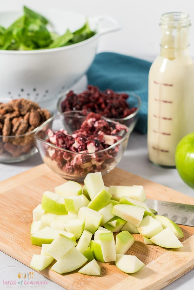 A green apple is diced on a cutting board.  A bowl of crumbled goat cheese in sits on the board.