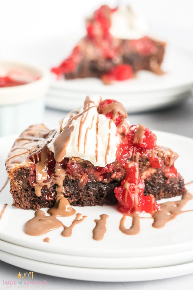 Brownie with whip cream, cherries and chocolate
