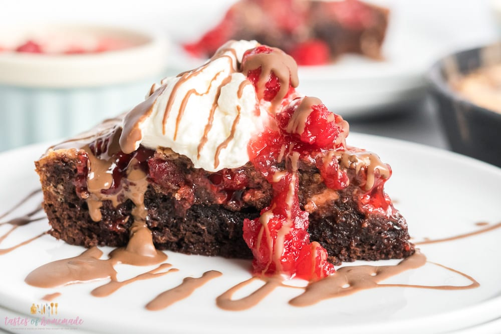 Black forest skillet brownie on a plate with whip cream, cherries and chocolate drizzle.