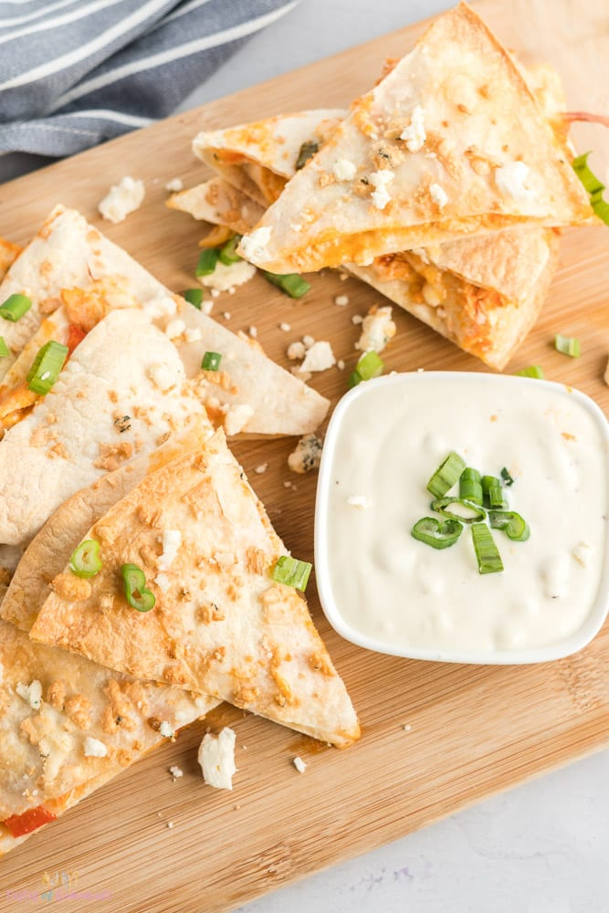buffalo chicken quesadillas cut into wedges with a dish of blue cheese dip.
