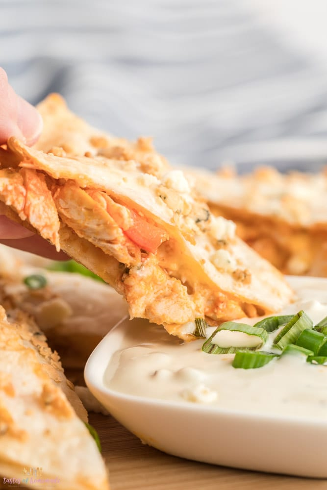 Buffalo chicken quesadilla being dipped in blue cheese.