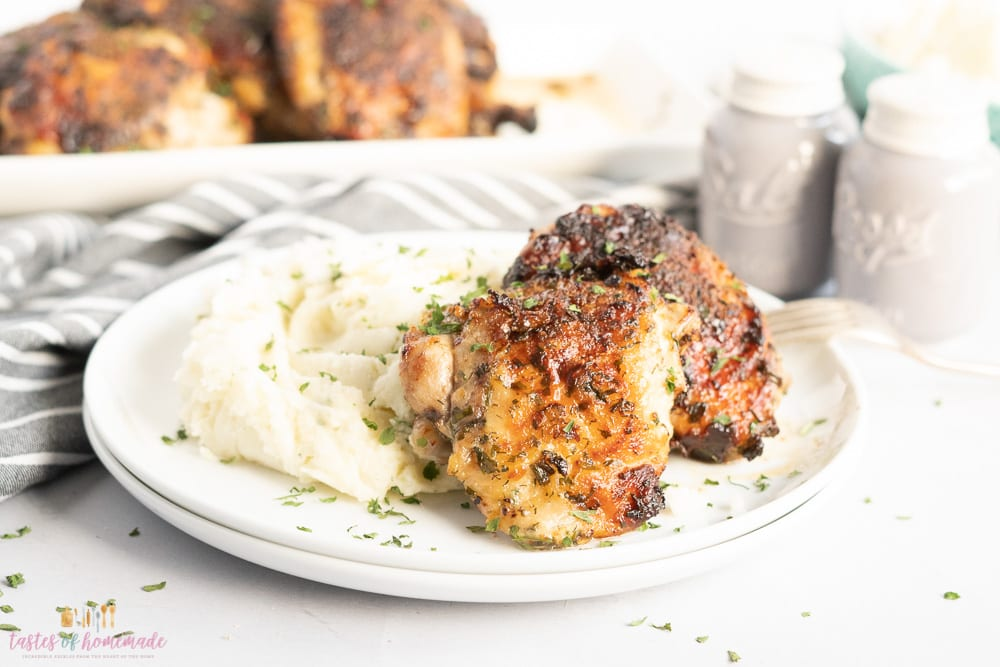 Ranch crusted air fried chicken thighs on a white plate with mashed potatoes
