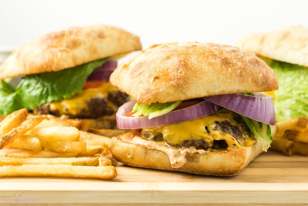 Skillet cheeseburgers with lettuce, tomato and red onions on ciabatta buns.