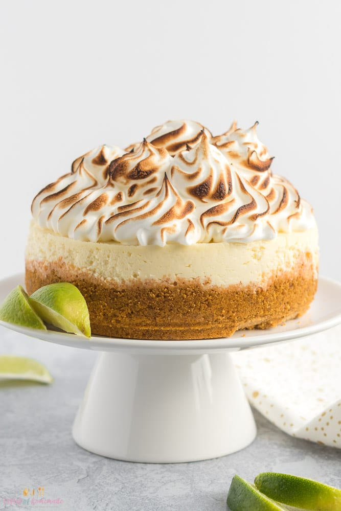 A side view of a lime cheesecake with toasted meringue sitting on a white cake stand.