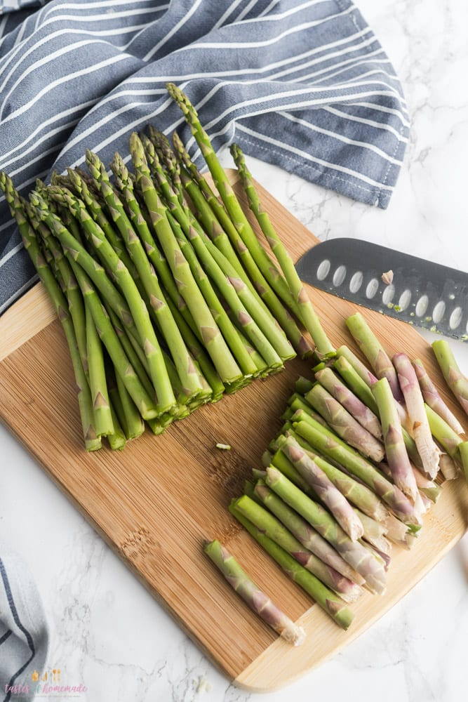 asparagus on a wooden chopping board with the ends cut off.