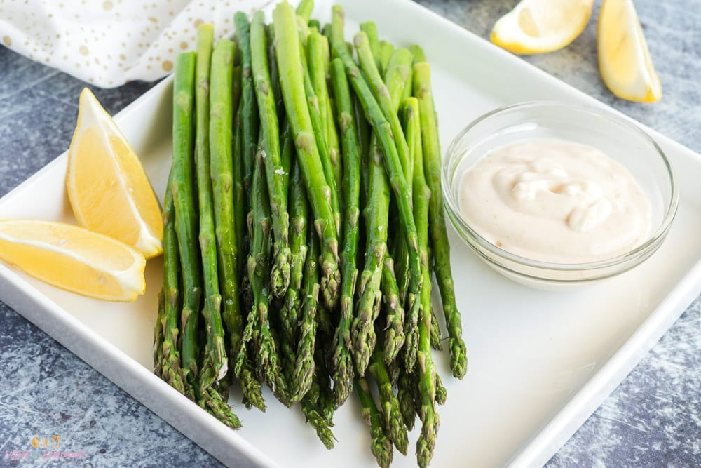 Air fried asparagus on a platter with lemon and garlic dip.