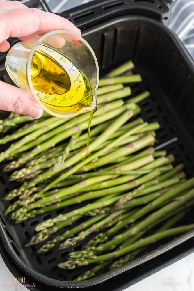 Asparagus in an air fryer basket being drizzled with olive oil