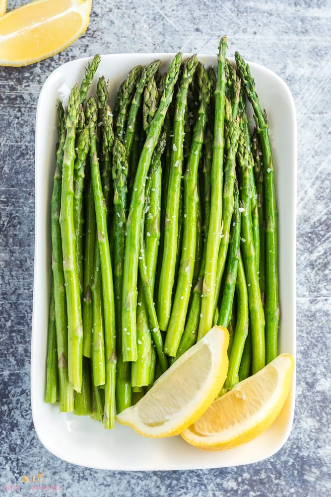 Air fried asparagus on a platter with lemon wedges.