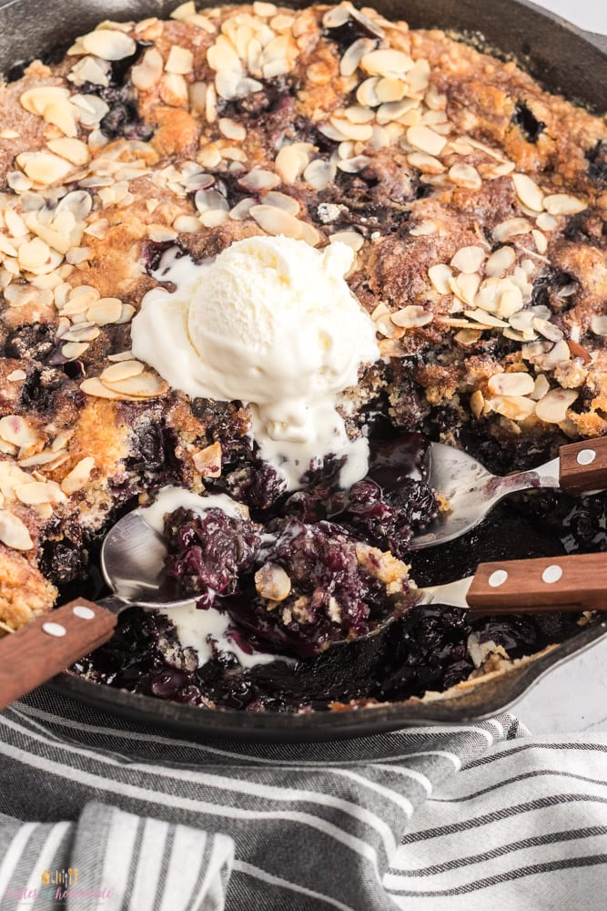 Blueberry dump cake in a cast iron skillet with a scoop of ice cream and 3 spoons.