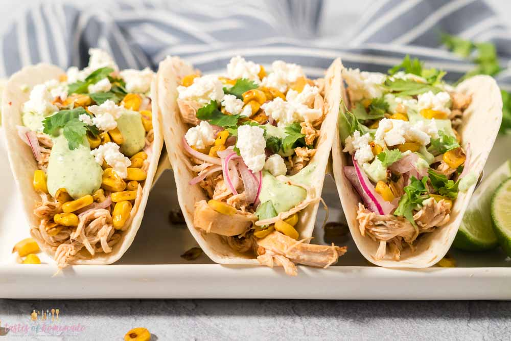 3 chicken tacos with corn, cilantro and cheese on a white plate.