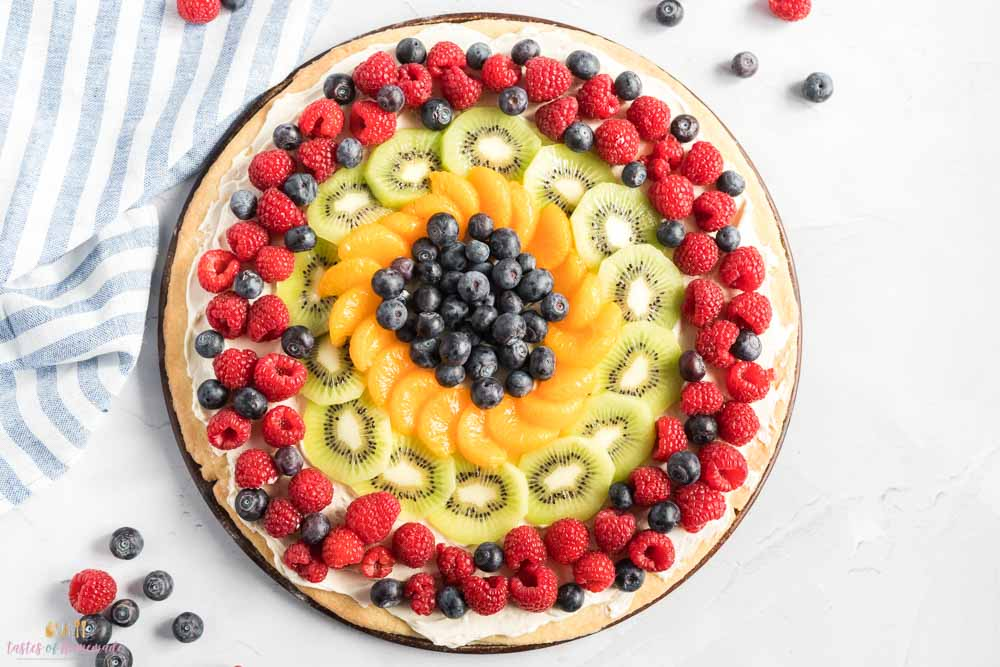 Fruit pizza on a round pizza stone. With raspberries, blueberries, kiwi and oranges.