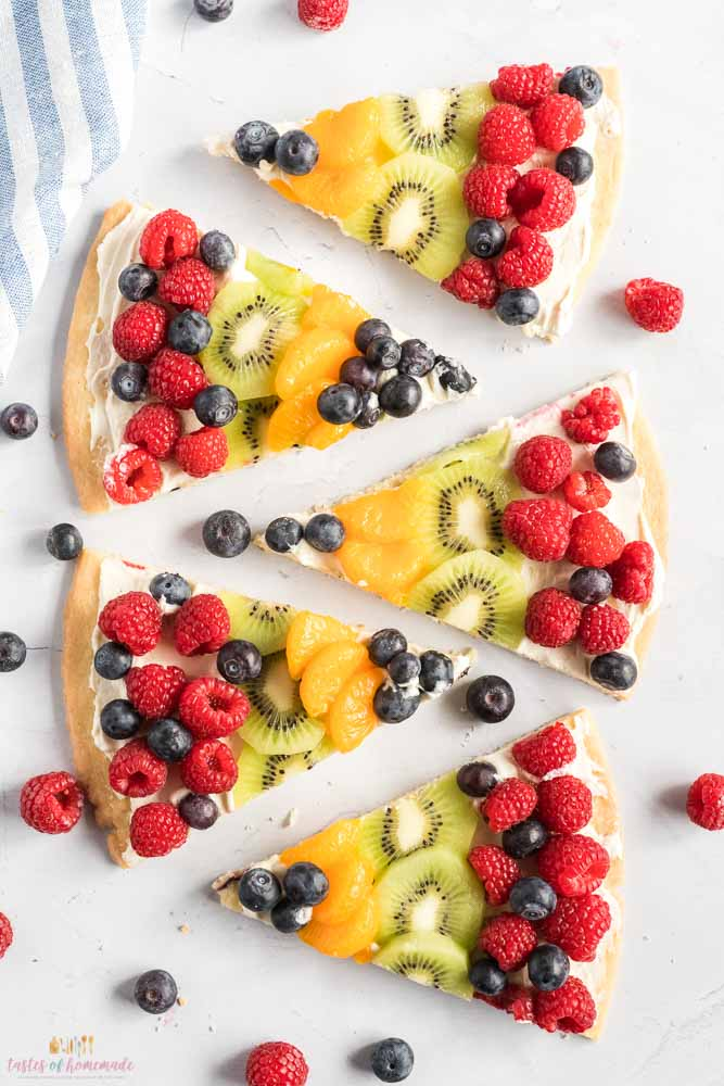 5 slices of fruit pizza on a table top.