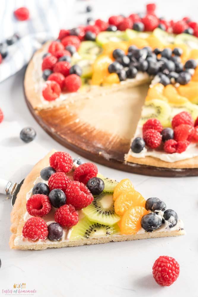 A slice of dessert pizza with fresh berries, orange and kiwi.