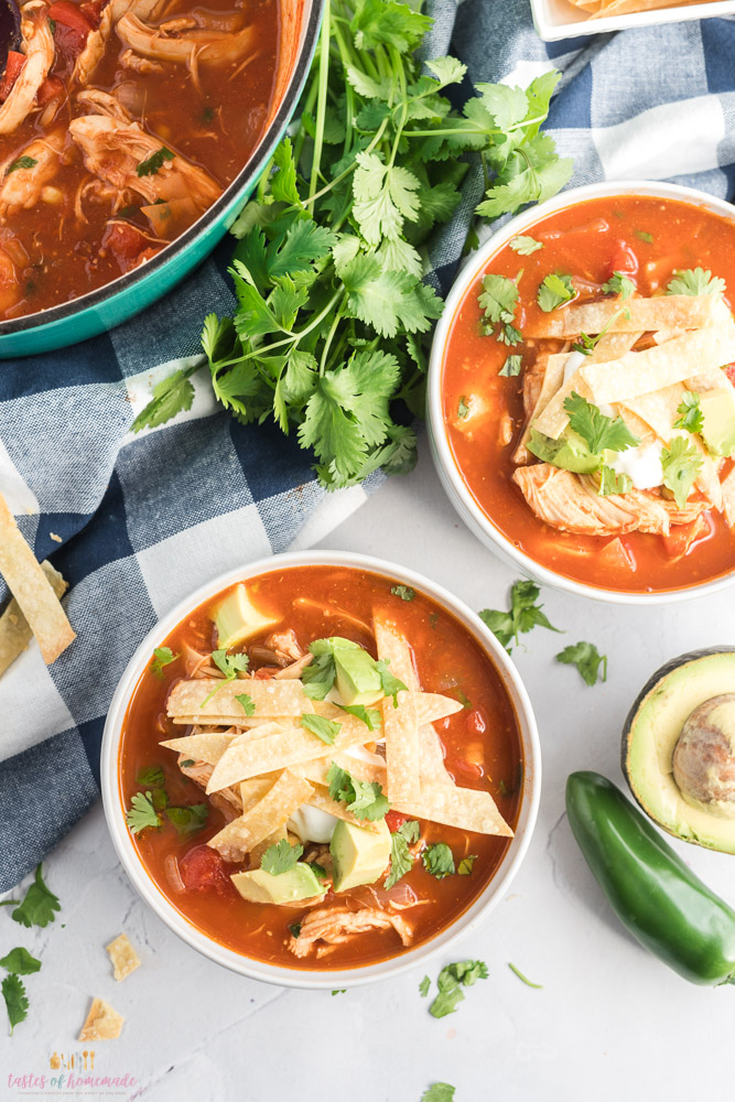 Chicken soup in tomato broth topped with tortilla strips and avocado