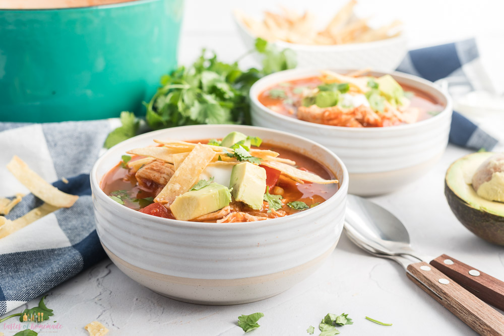 Two bowls of chicken tortilla soup topped with tortilla strips and avocado