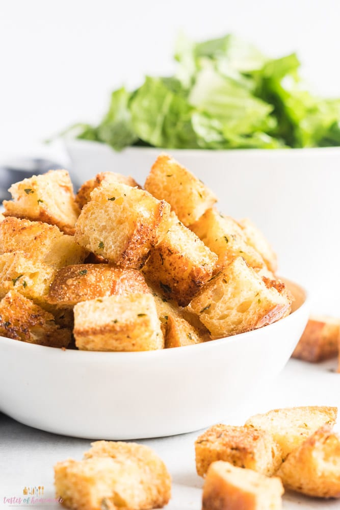Croutons in a white bowl with salad in the background