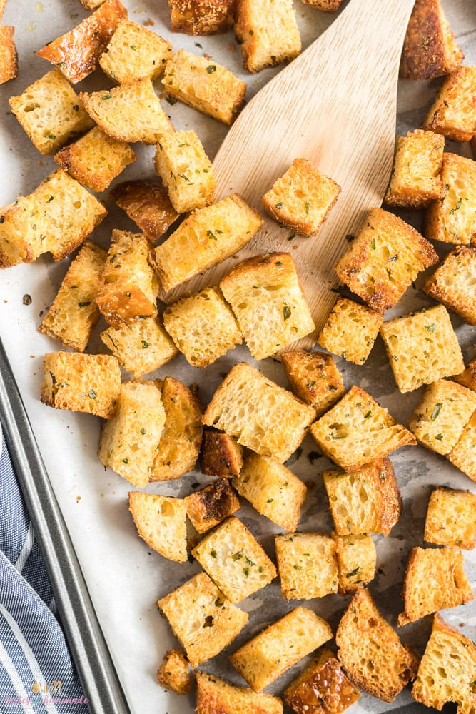 Croutons on a baking sheet with a wooden spoon
