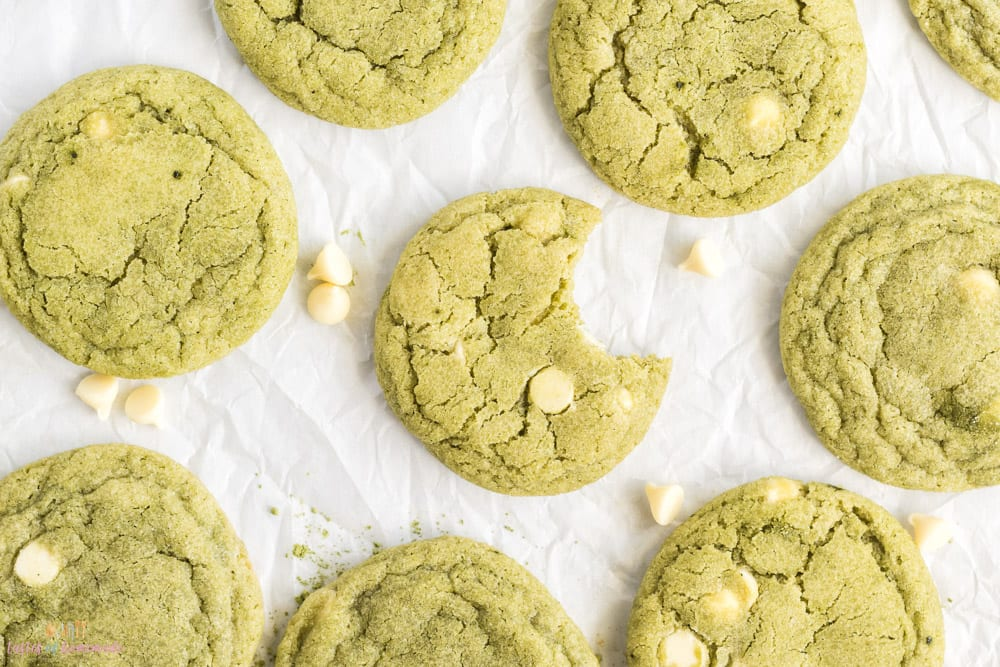 Matcha cookies spread out on a white background
