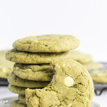 Stack of cookies on a white plate with a bite out of one cookie