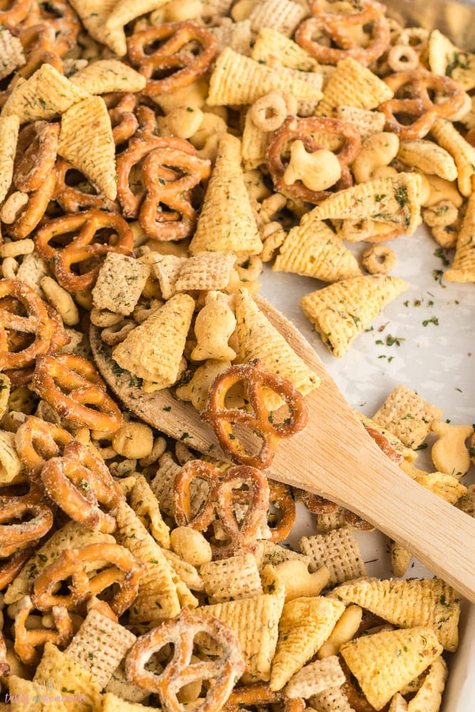Snack mix on a baking sheet with a wooden spoon