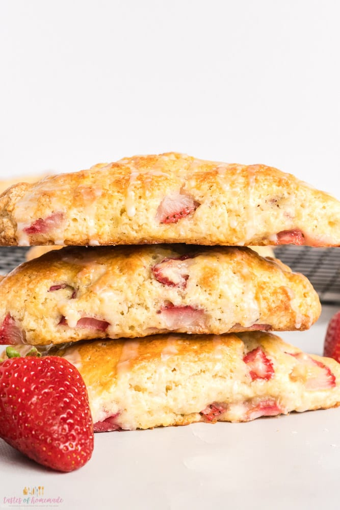 3 strawberry rhubarb scones in a stack.  A fresh strawberry in front.