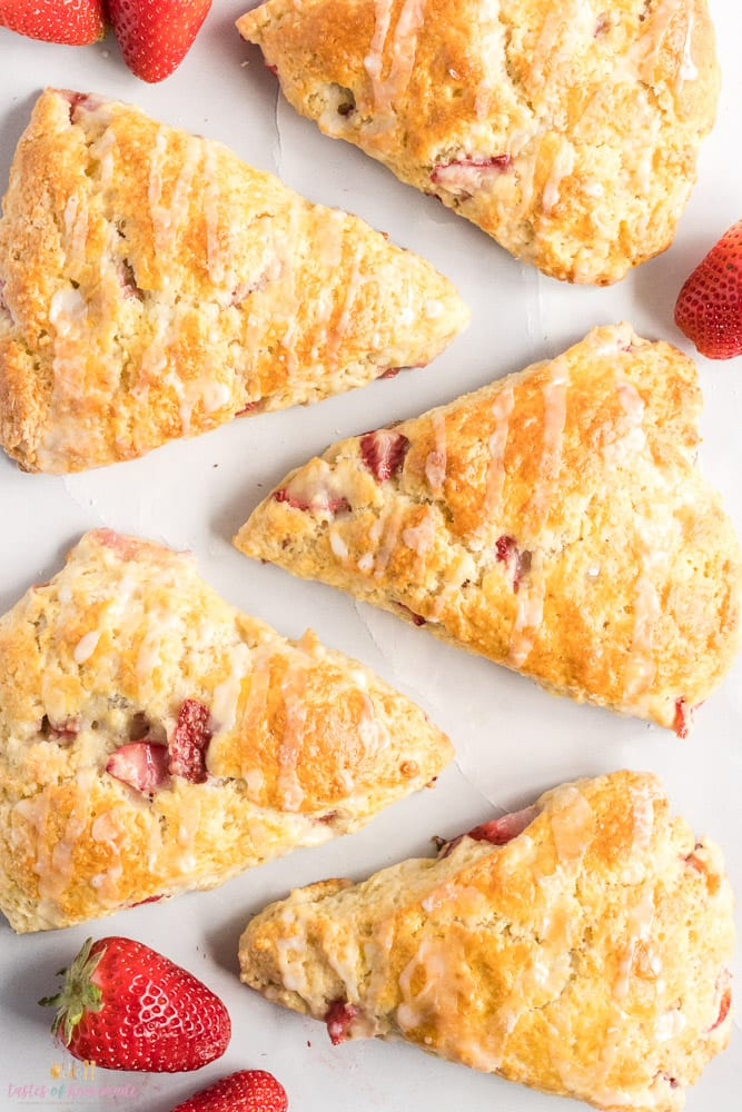 Strawberry rhubarb scones on a counter top with fresh strawberries scattered