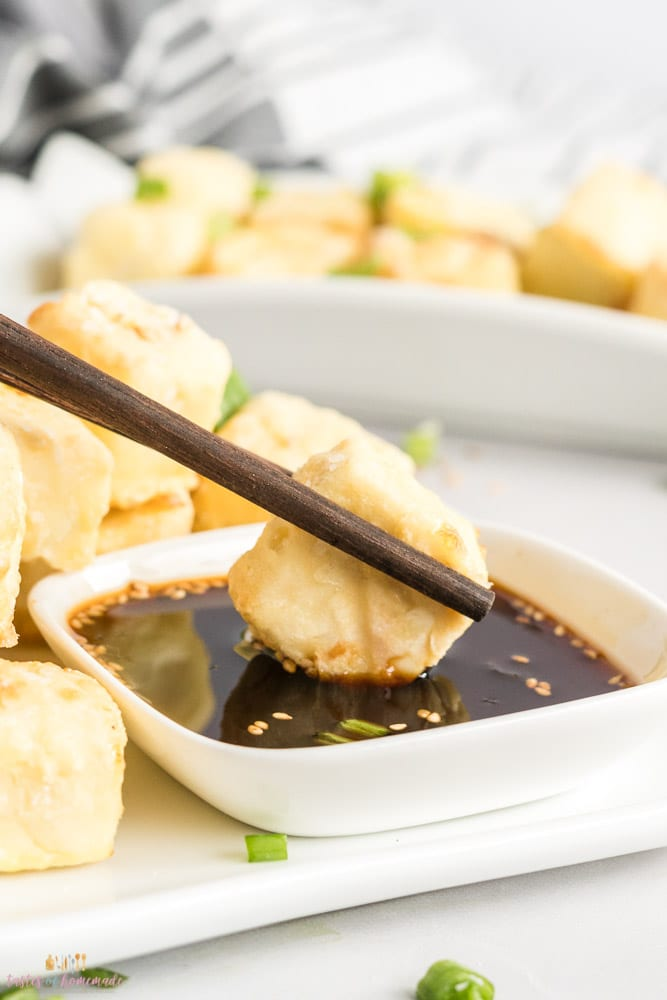 tofu nugget being dipped in soy sauce