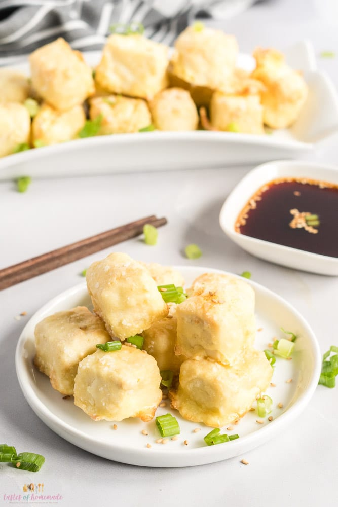 Breaded tofu on a white plate with chopsticks and a dish of soy sauce
