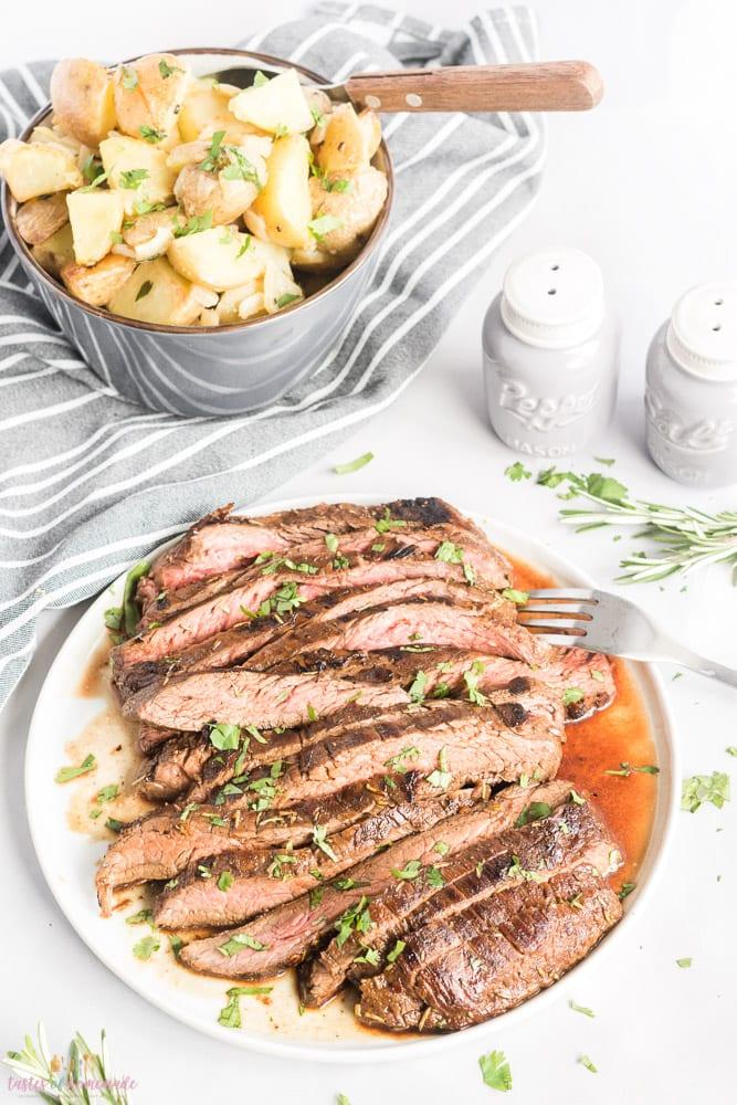Meal of sliced steak, & potatoes, chopped parsley garnish.