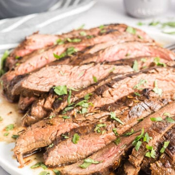 Close up of sliced flank steak with chopped parsley