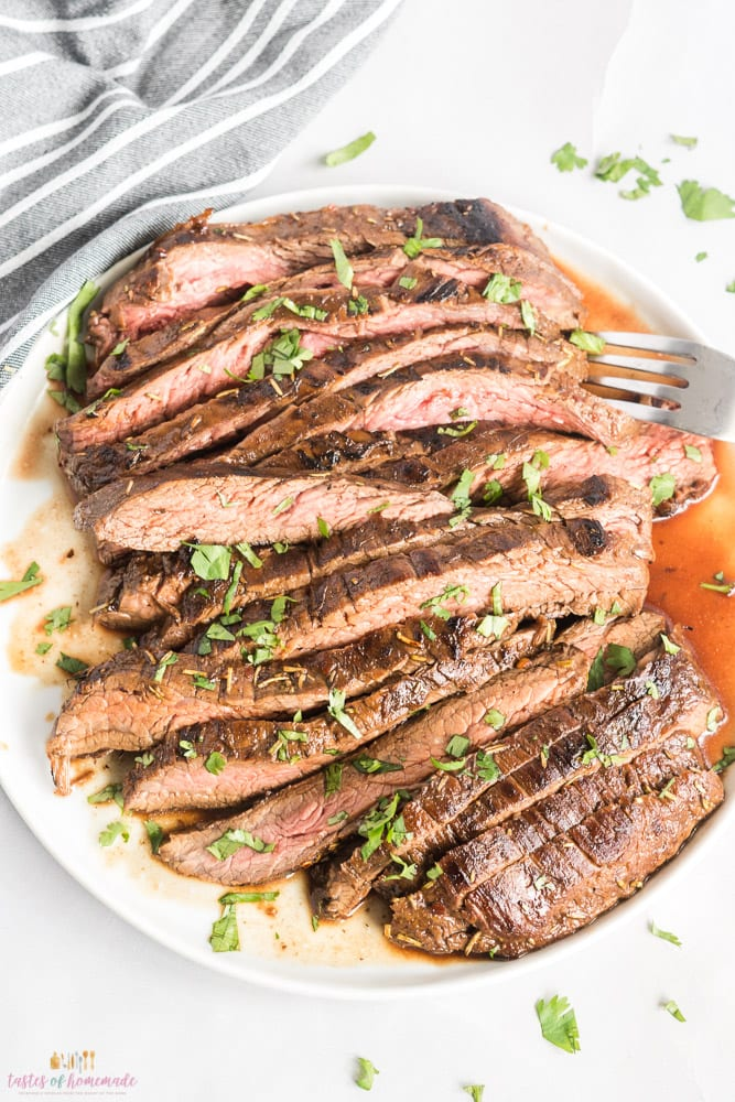 Sliced steak on a white plate with chopped parsley garnish