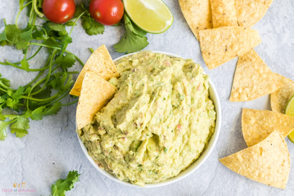 Bowl of guacamole with tortilla chips, cherry tomatoes and fresh cilantro on the table