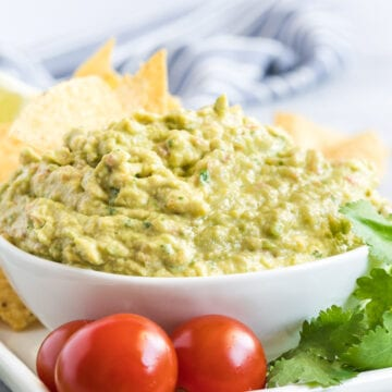 Guacamole in a white bowl with cherry tomatoes