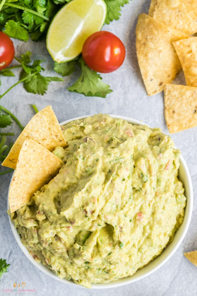 Guacamole in a bowl with limes, cherry tomatoes and tortilla chips on the side