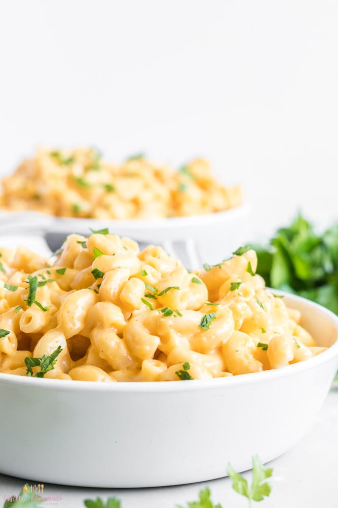 Mac and cheese in a white bowl with a sprinkle of parsley