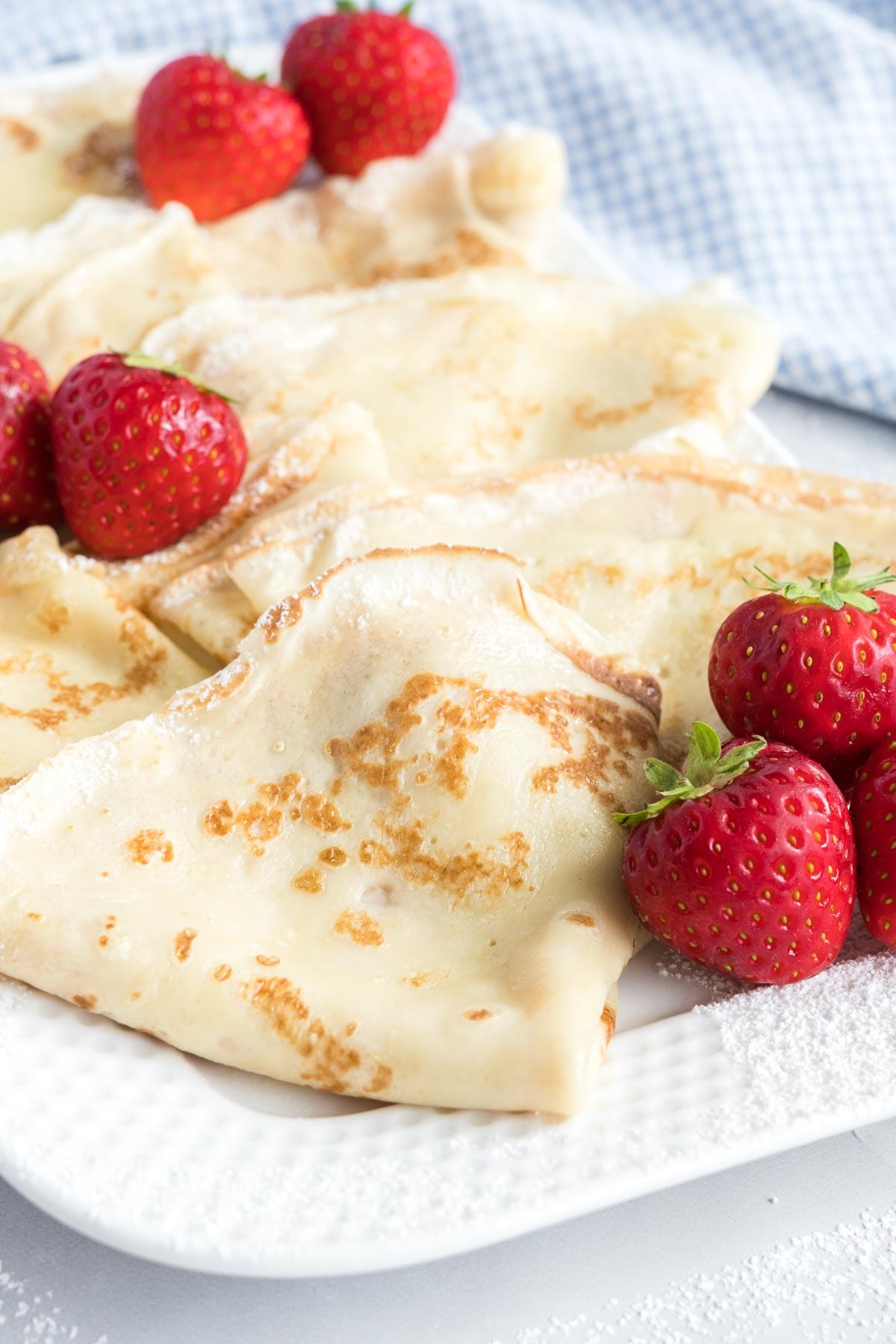 Folded crepes on a platter with fresh strawberries.