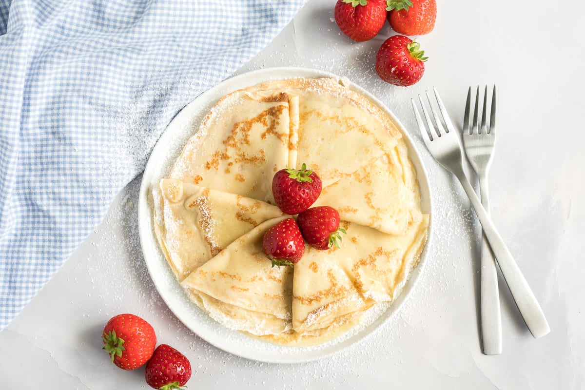 Crepes on a round plate garnished with strawberries and powdered sugar.