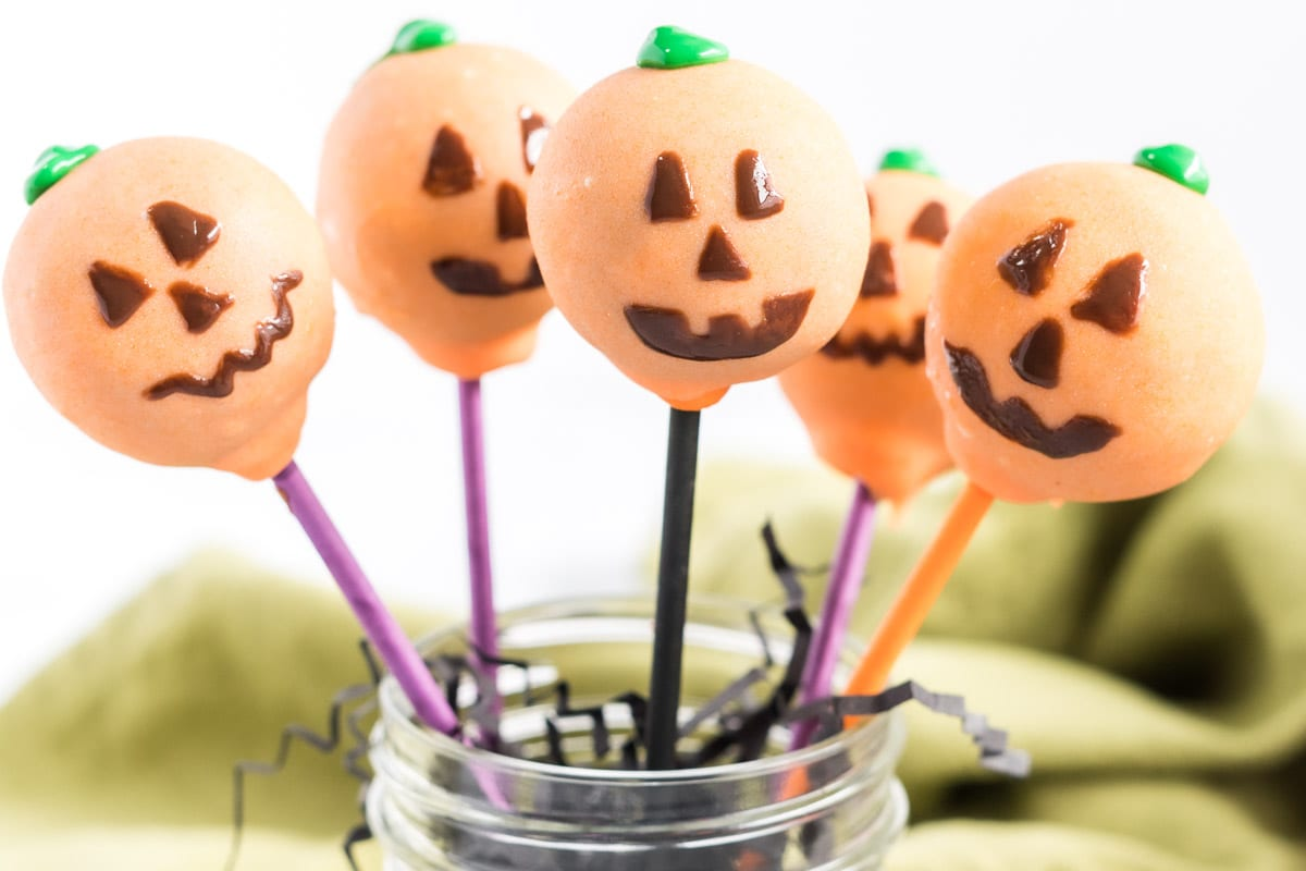 5 Jack-O-Lantern cake pops in a jar.