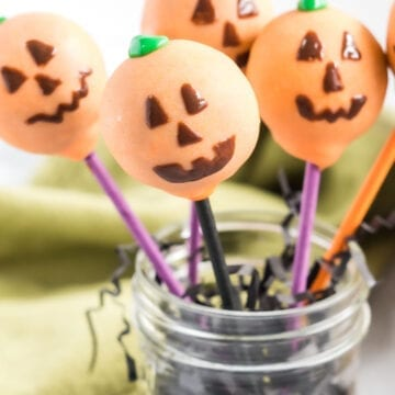 Close up of jack-o-lantern decorated cake pop in decorative jar.