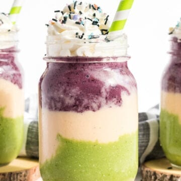 Smoothie layered in green, orange and purple with whip cream.